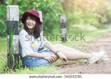 Asian woman sitting on a park kilometers near a countryside road,Travel life style