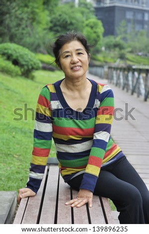 asian woman sitting on bench,outdoors. - stock photo