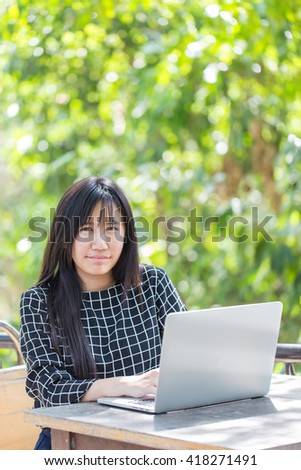 Asian woman sitting on chair at coffee shop in outdoor zone and she works on a laptop