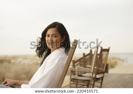 Asian woman sitting on deck at beach - stock photo
