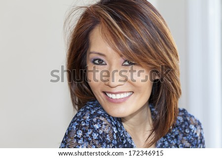 Asian woman smiling at the camera - stock photo
