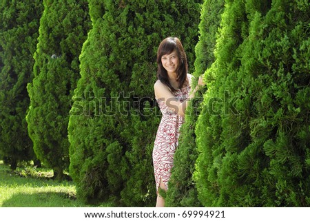 asian woman smiling in the park behind the tree