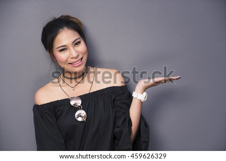 Asian woman smiling portrait and showing empty copy space with glasses on her dress - stock photo