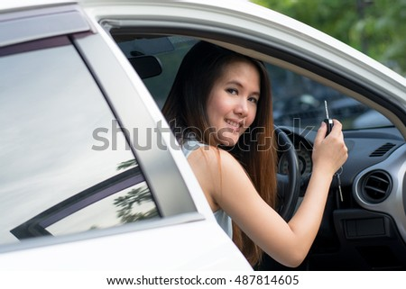 Asian woman smiling showing new car keys and car.