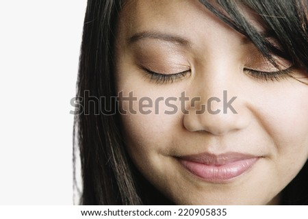 Asian woman smiling with eyes closed - stock photo