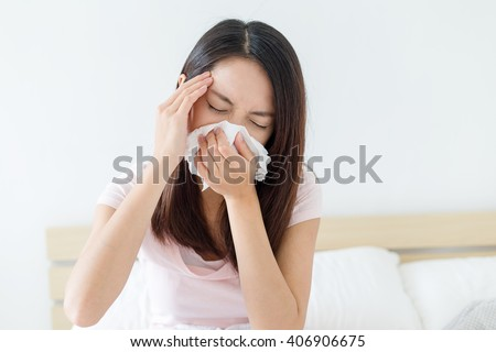 Asian woman sneezing on bed - stock photo