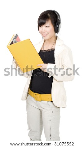 Asian woman standing and holding yellow book and listening music headphones - stock photo
