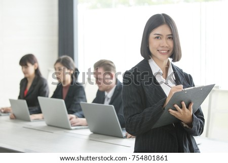 Asian Woman standing in front of her team with smiling, Female with her team working in the office, 