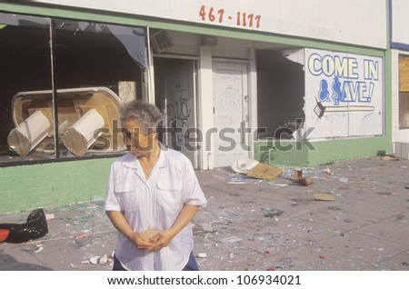 Asian woman standing in front of store looted during 1992 riots, South Central Los Angeles, California - stock photo