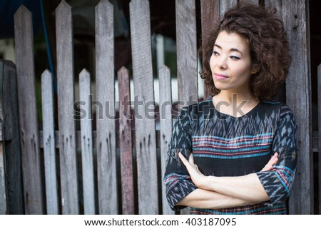 Asian woman stands near the wooden fence.