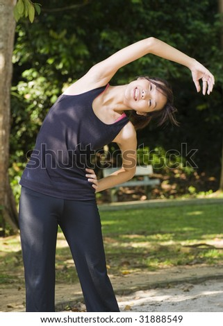asian woman stretching her body during warm up - stock photo