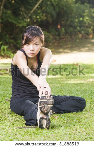 asian woman stretching her leg muscles