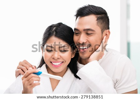 Asian woman surprising her husband with positive pregnancy test, he seems reasonably pleased - stock photo