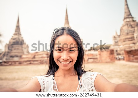 Asian woman taking a selfie at temple in Ayutthaya, Thailand - Tourist recording while sightseeing in Asia  - stock photo