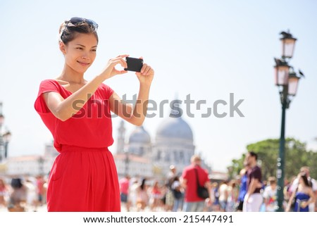 Asian woman taking picture photo with smartphone in Venice, Italy. Tourist girl using smart phone camera to take photograph on travel in Europe. - stock photo