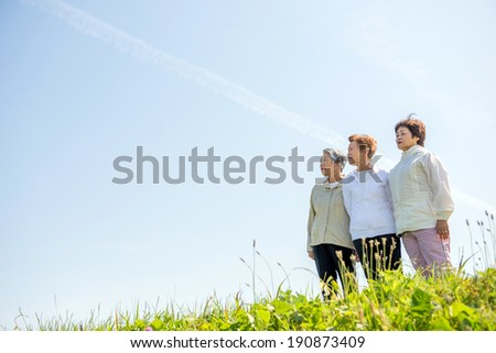 Asian woman threesome of elderly overlooking the sky - stock photo