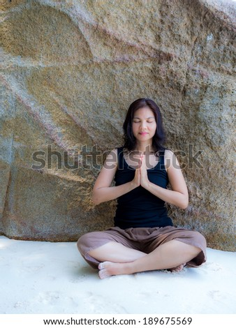 Asian woman training yoga and meditation in front of the rock at the beach - stock photo