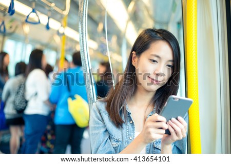 Asian woman use of mobile phone in Hong Kong metro - stock photo