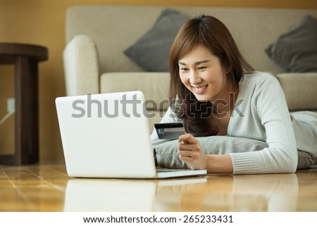 Asian woman using laptop at home - stock photo