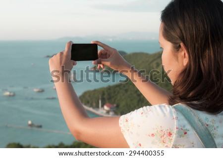 asian woman using smart phone take a photo at koh larn island  in Pattaya ,Thailand - stock photo