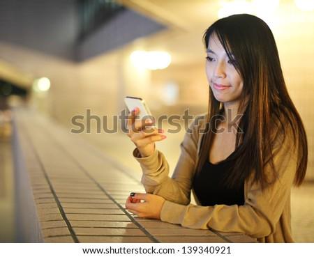 Asian woman using smartphone at night - stock photo