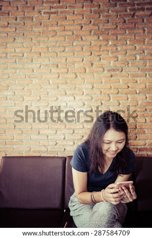 Asian woman using smartphone happy in the cafe, Modern lifestyle, Process color vintage - stock photo