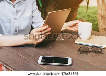 Asian woman using tablet in garden at coffee shop with vintage tone.