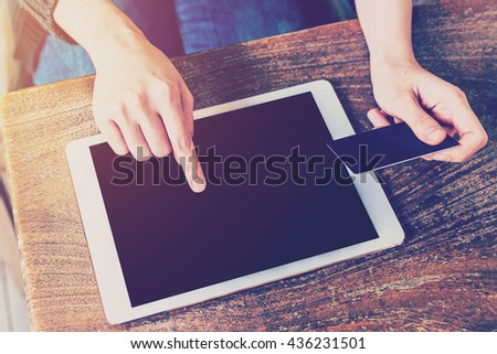 asian woman using tablet paying credit card with vintage toned. - stock photo