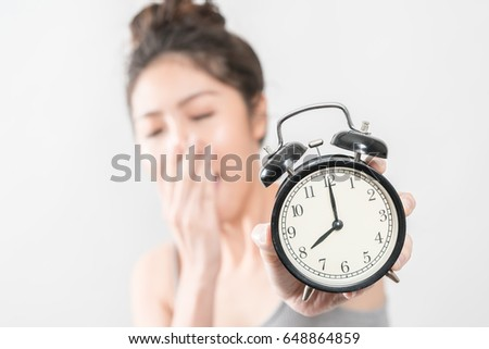 Asian woman waking up, the alarm clock waking up in the morning from a call