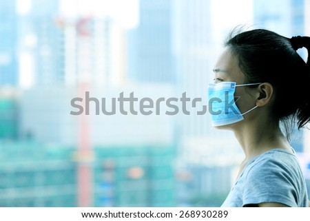 asian woman wear face mask in pollution city - stock photo