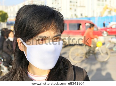 Asian woman wearing a face mask to protect against disease and pollution - stock photo