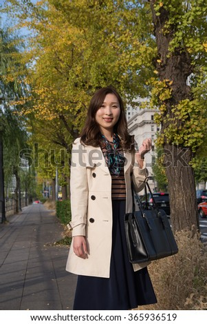 asian woman wearing coat in the park