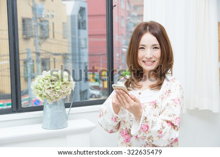 asian woman wearing Pajamas with smartphone