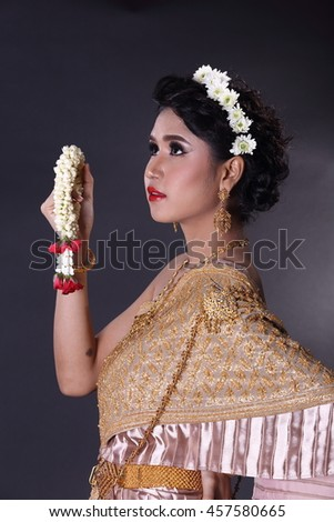 Asian woman wearing traditional antique Thai dress. Studio lighting with dark background.