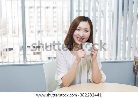 asian woman with a cup of coffee
