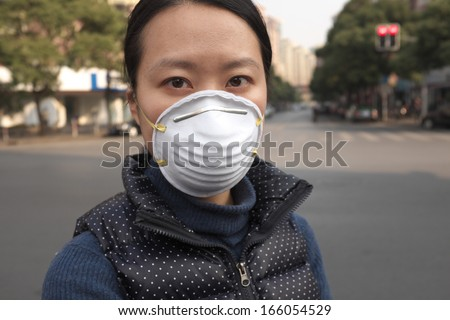 Asian woman with a face mask on a street - stock photo
