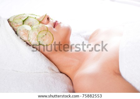 asian woman with a facial mask and cucumber on her face
