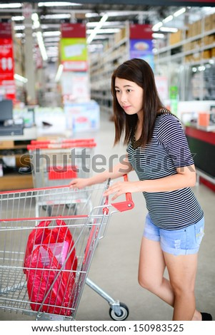 Asian woman with a shopping cart at the supermarket