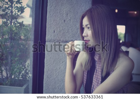 Asian woman with coffee cup in coffee shop. Woman drinking coffee in coffee shop Vintage Tone.