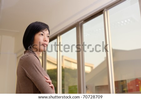 Asian woman with confident expression, closeup portrait indoor.