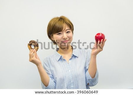 asian woman with donut and apple