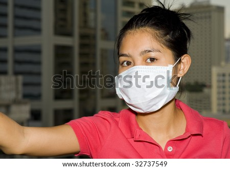 asian woman with face mask in front of the bangkok skyline - stock photo