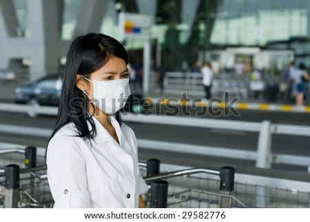 asian woman with face mask in front of the international airport in bangkok - stock photo