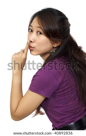 Asian Woman with finger on lips. She has a secret. She wearing purple shirt