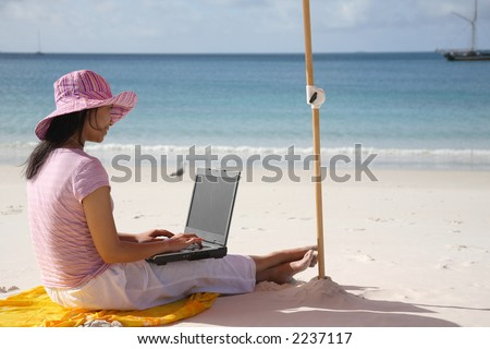 Asian woman with pink hat working on the beach in Queensland, Australia