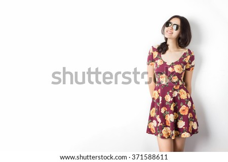 Asian woman with sunglasses and vintage flora dress standing by the wall. - stock photo