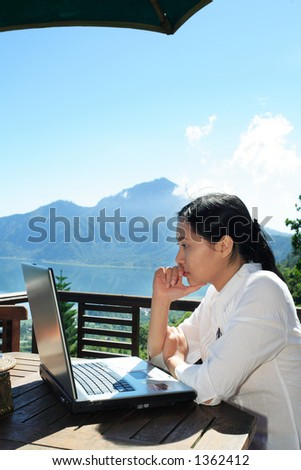 Asian woman working at a restaurant with a mountain in the background.