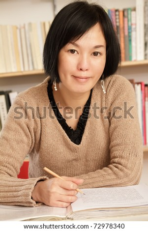 Asian woman working at home with smiling expression on face.