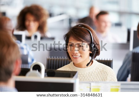 Asian woman working in call centre, surrounded by colleagues - stock photo