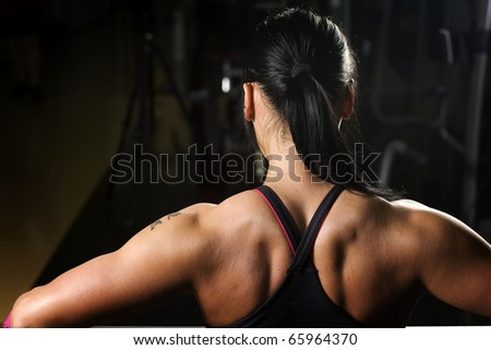 Asian woman working out in gym from behind - stock photo